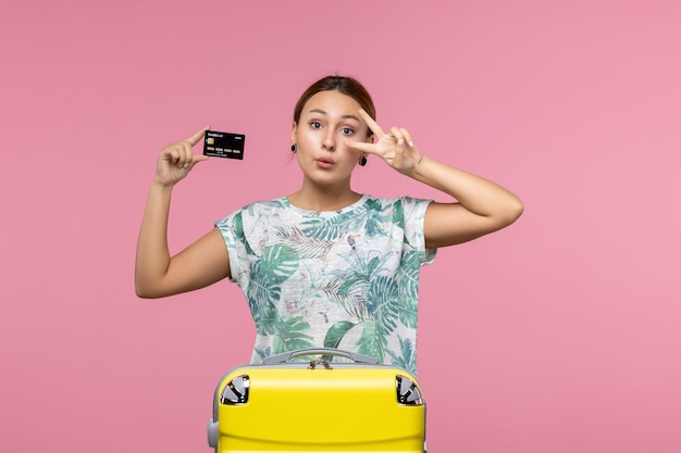 연분홍 벽에 은행 카드를 들고 있는 젊은 여성의 전면 모습