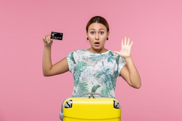 분홍색 벽에 검은색 은행 카드를 들고 있는 젊은 여성의 전면 모습