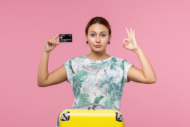 밝은 분홍색 벽에 검은색 은행 카드를 들고 있는 젊은 여성의 전면 모습