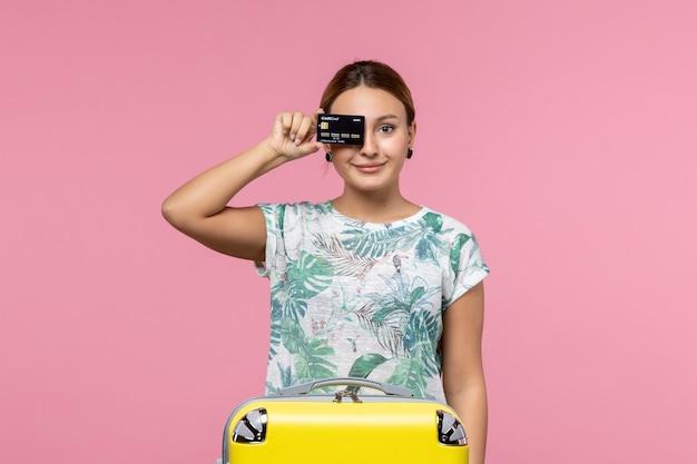 ピンクの壁に黒い銀行カードを保持している若い女性の正面図