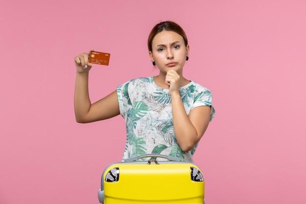 淡いピンクの壁に茶色の銀行カードを保持している若い女性の正面図