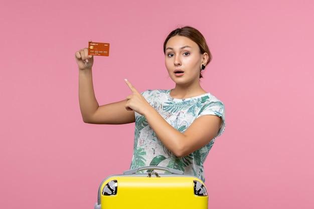 Вид спереди молодой женщины, держащей коричневую банковскую карту на розовой стене