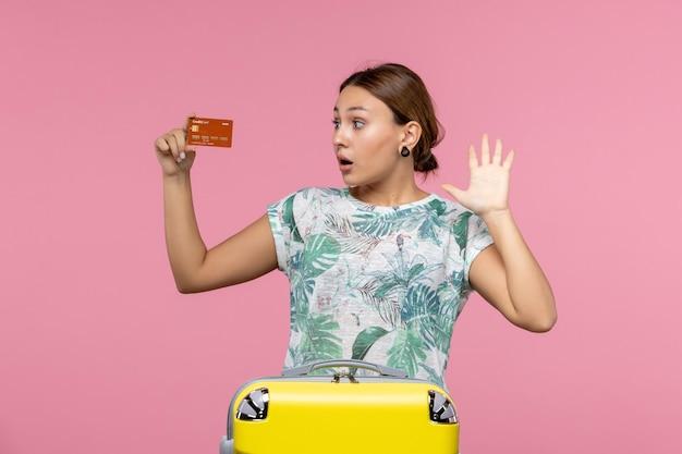 분홍색 벽에 갈색 은행 카드를 들고 있는 젊은 여성의 전면 모습