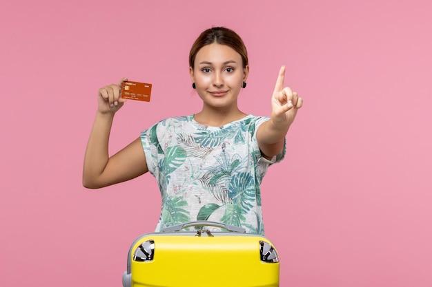 Вид спереди молодой женщины, держащей коричневую банковскую карту с улыбкой на розовой стене