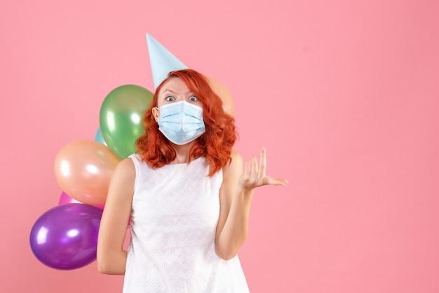 ピンクの壁に滅菌マスクでカラフルな風船を保持している若い女性の正面図