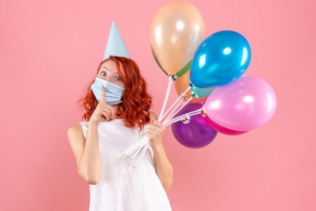 분홍색 벽에 멸균 마스크에 다채로운 풍선을 들고 젊은 여자의 전면보기