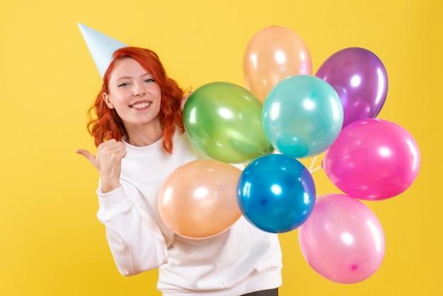 Вид спереди молодой женщины, держащей разноцветные шары на желтой стене