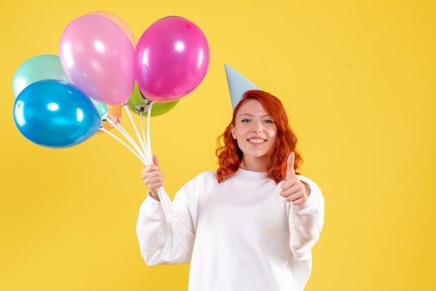 Вид спереди молодой женщины, держащей милые разноцветные шары на желтой стене