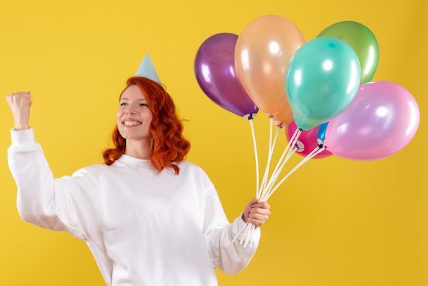 노란색 벽에 귀여운 다채로운 풍선을 들고 젊은 여자의 전면보기