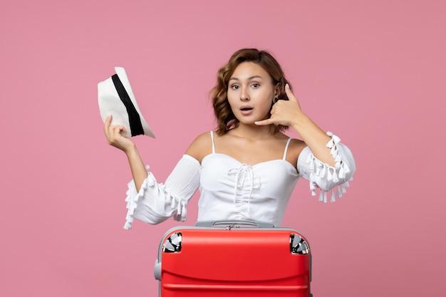 帽子をかぶって、淡いピンクの壁に赤いバッグで旅行の準備をしている若い女性の正面図