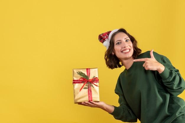 黄色の壁に小さなクリスマスプレゼントを保持している若い女性の正面図
