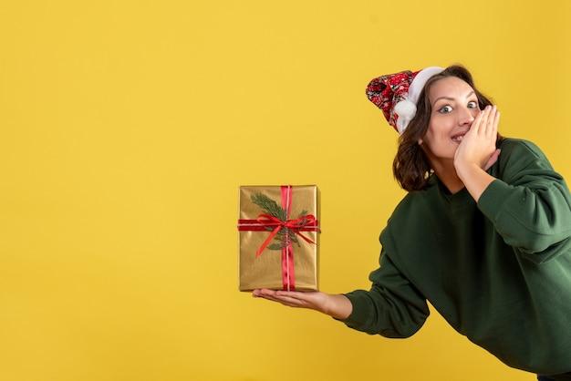 Вид спереди молодой женщины, держащей маленький рождественский подарок на желтой стене