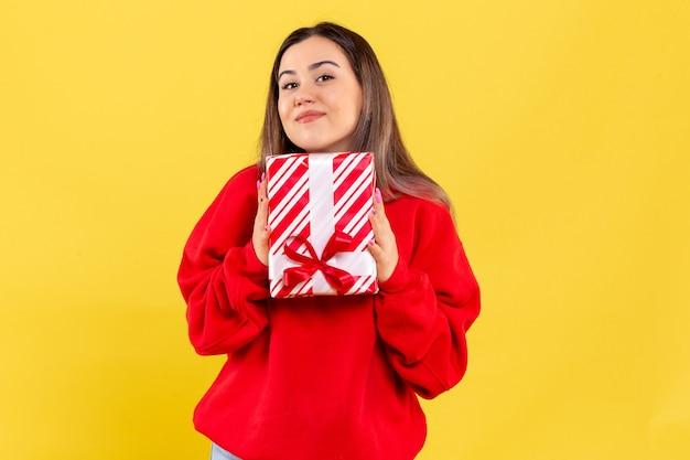 Вид спереди молодой женщины, держащей маленький подарок на желтой стене