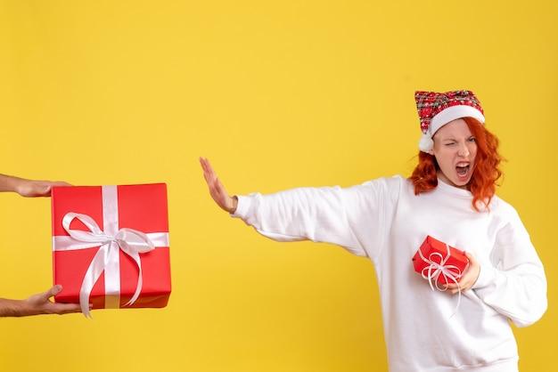 黄色の壁に小さなプレゼントを保持し、大きなものを拒否する若い女性の正面図