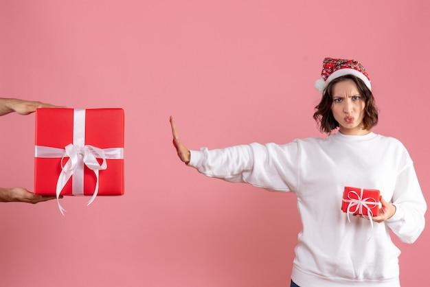 Вид спереди молодой женщины, держащей маленький подарок и отвергающей подарок от мужчины на розовой стене