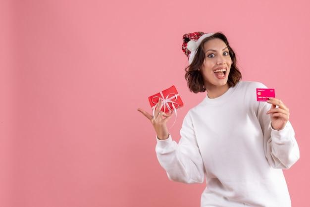 분홍색 벽에 작은 크리스마스 선물 및 은행 카드를 들고 젊은 여자의 전면보기