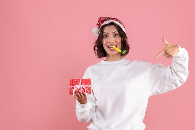 ピンクの壁に存在する小さなクリスマスを保持している若い女性の正面図