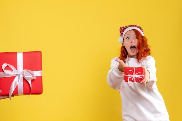 黄色の壁に存在する小さなクリスマスを保持している若い女性の正面図