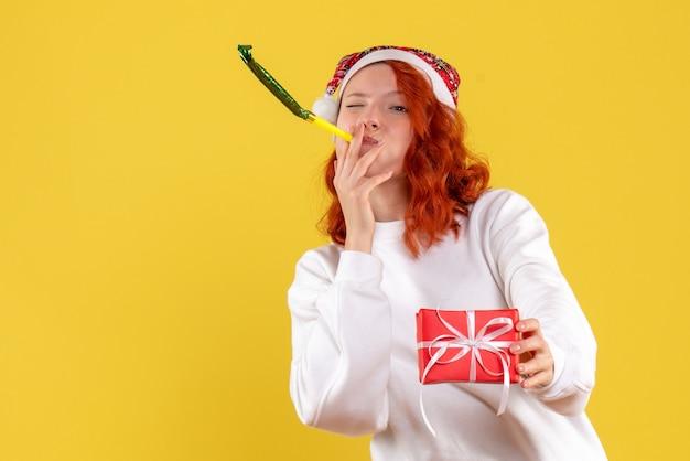 노란색 벽에 작은 크리스마스 선물을 들고 젊은 여자의 전면보기