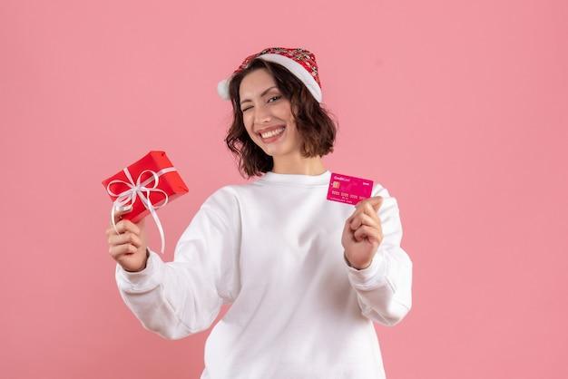 분홍색 벽에 작은 크리스마스 선물 은행 카드를 들고 젊은 여자의 전면보기