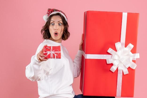 분홍색 벽에 거대한 하나 선물 작은 크리스마스를 들고 젊은 여자의 전면보기