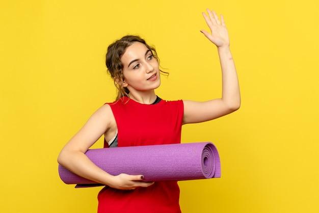 紫色のカーペットを保持し、黄色の壁に手を振って若い女性の正面図