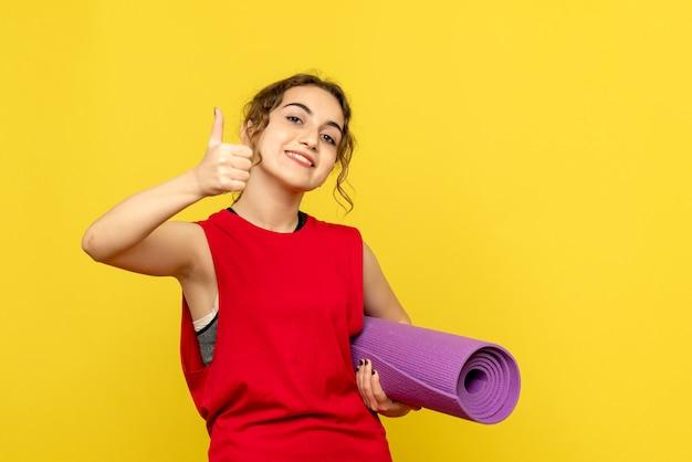 Вид спереди молодой женщины, держащей фиолетовый ковер на желтой стене