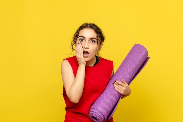 노란색 벽에 보라색 카펫을 들고 젊은 여자의 전면보기