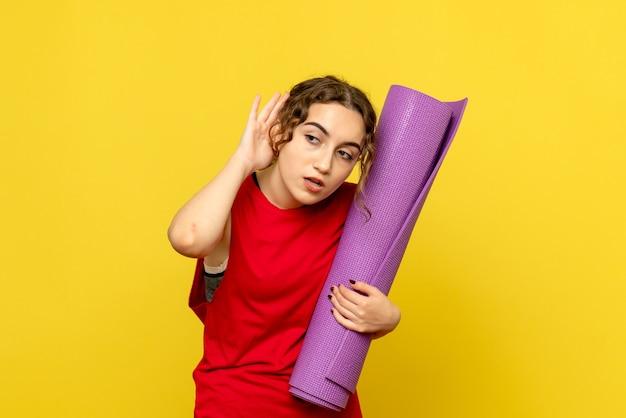 黄色の壁に紫色のカーペットを保持している若い女性の正面図