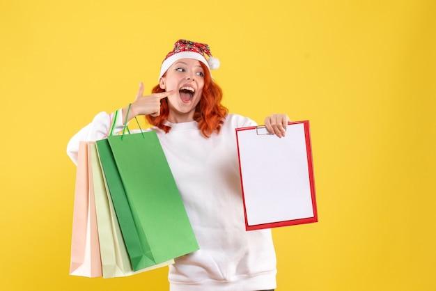 黄色の壁にショッピングパッケージを保持している若い女性の正面図