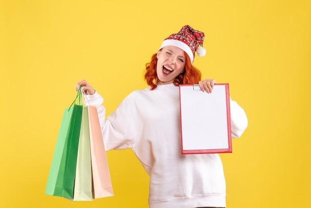 노란색 벽에 쇼핑 패키지를 들고 젊은 여자의 전면보기