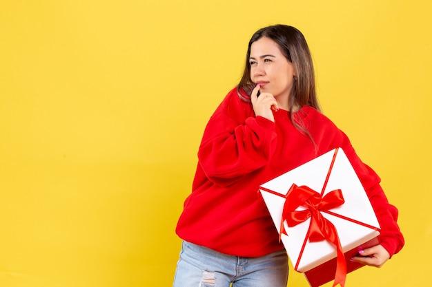 Вид спереди молодой женщины, держащей рождественский подарок на желтой стене