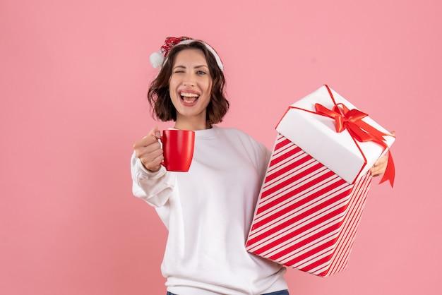 크리스마스 선물과 분홍색 벽에 차 한잔 들고 젊은 여자의 전면보기