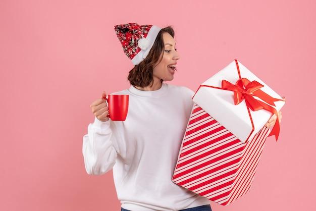 Вид спереди молодой женщины, держащей рождественский подарок и чашку чая на розовой стене