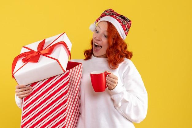 Вид спереди молодой женщины, держащей рождественский подарок и чашку чая на желтой стене