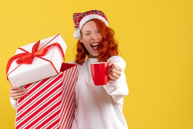 크리스마스 선물과 노란색 벽에 차 한잔 들고 젊은 여자의 전면보기