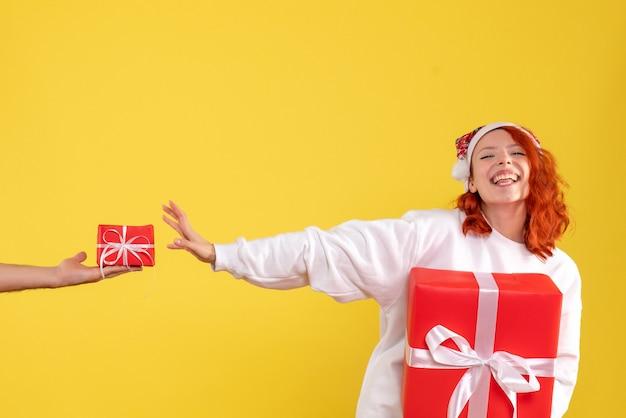 노란색 벽에 크리스마스 선물을 들고 젊은 여자의 전면보기