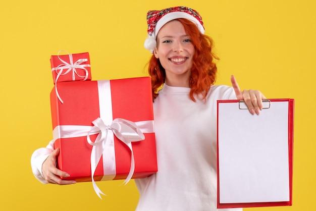 노란색 벽에 크리스마스 선물 및 파일 메모를 들고 젊은 여자의 전면보기