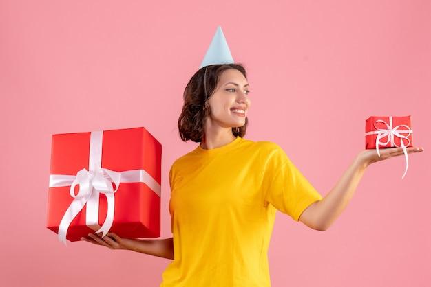 분홍색 벽에 크리스마스 선물을 들고 젊은 여자의 전면보기