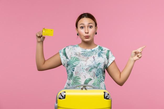 Вид спереди молодой женщины, держащей желтую банковскую карту на розовой стене