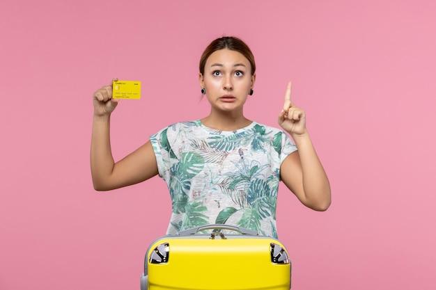 ピンクの壁に黄色の銀行カードを保持している若い女性の正面図