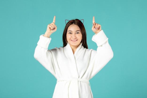 青い壁にバスローブを着た若い女性の正面図