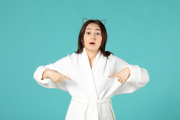 파란색 벽에 목욕 가운을 입은 젊은 여성의 전면 모습
