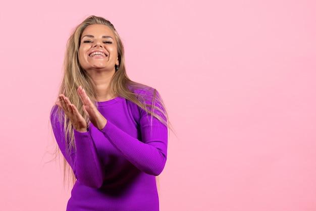 Вид спереди молодой женщины в красивом фиолетовом платье, позирующей на розовой стене