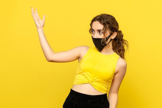 Вид спереди молодой женщины в черной маске на стене y ellow