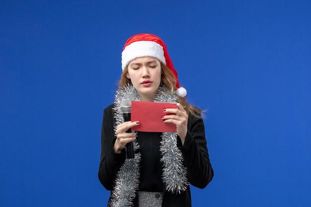 青い壁に封筒とカラオケパーティーで若い女性の正面図