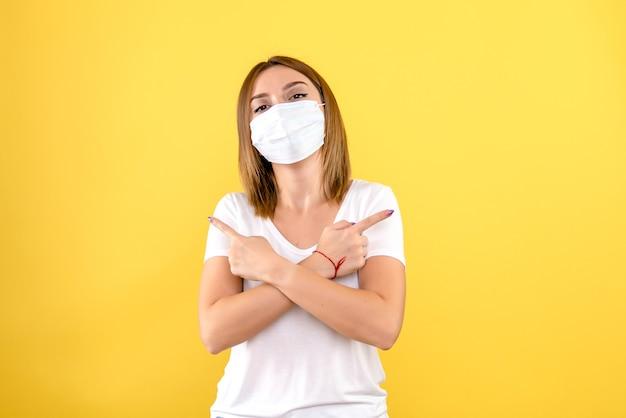 黄色の壁にマスクで若い女性の正面図