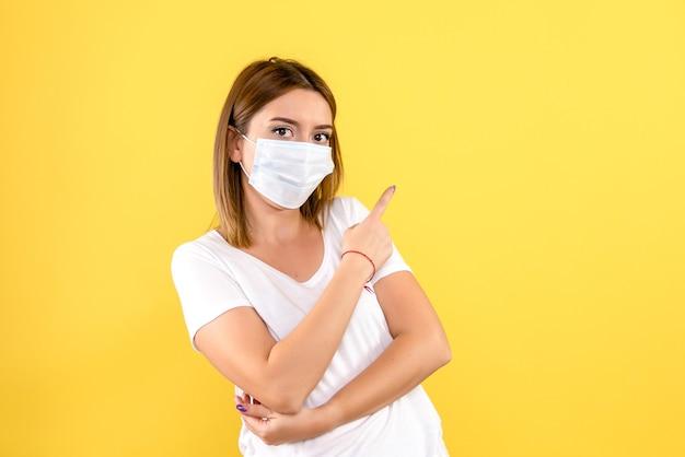 Вид спереди молодой женщины в маске на желтой стене