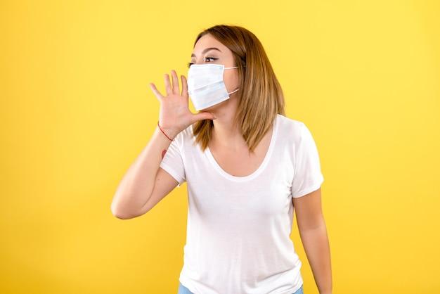 노란색 벽에 마스크에 젊은 여자의 전면보기