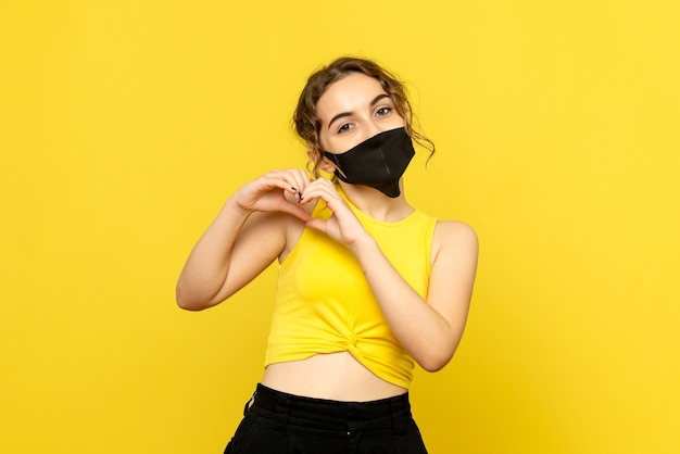 黄色の壁に愛を送るマスクの若い女性の正面図